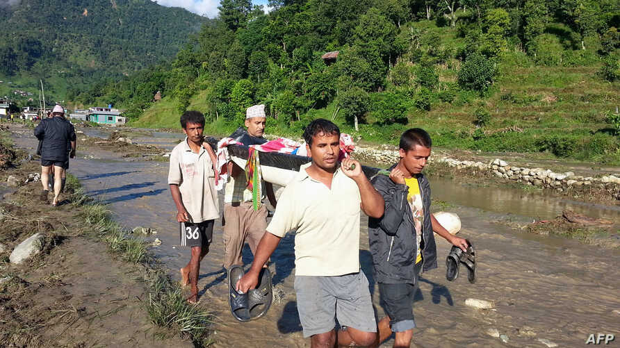 Nepalese villagers carry a landslide survivor in the Kaski district of western Nepal on July 30, 2015. Landslides triggered by heavy rains killed at least 24 people on July 30 and left more than a dozen missing as homes were swept away in three distr