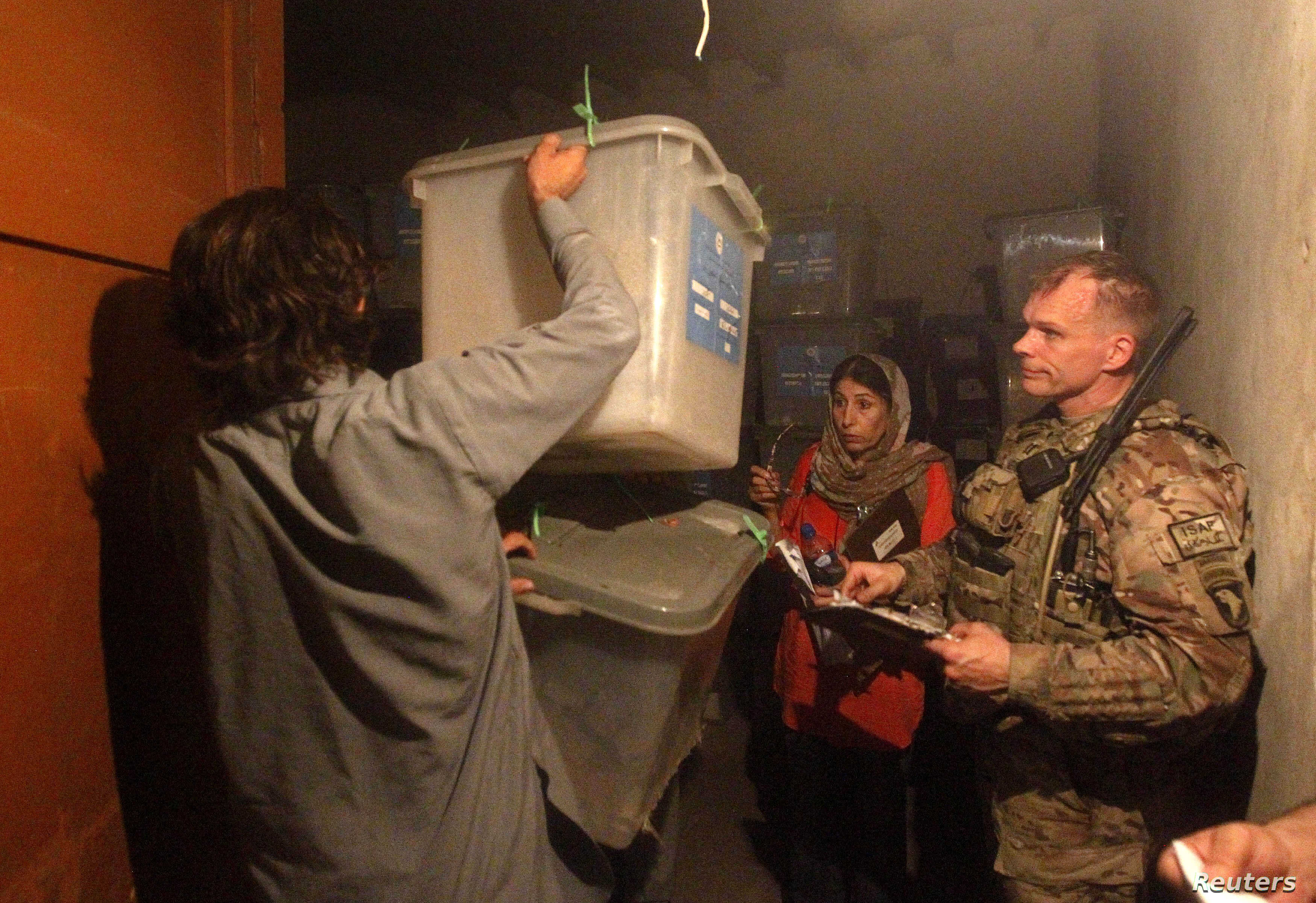 A U.S. soldier from the NATO International Security Assistance Force (ISAF) checks the serial numbers of ballot boxes being transferred to Kabul for an audit of the presidential run-off, Jalalabad province, July 20, 2014.
