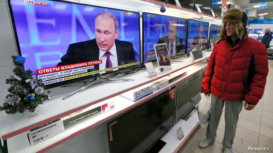 """FILE - A customer stands near TV sets during the annual end-of-year news conference of Russian President Vladimir Putin at the """"Pozitronika"""" electronic store in Russia's Siberian town of Divnogorsk."""