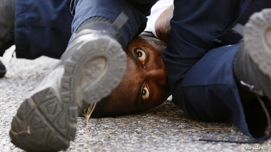 A man protesting the shooting death of Alton Sterling is detained by law enforcement near the headquarters of the Baton Rouge Police Department in Baton Rouge, Louisiana, July 9, 2016.