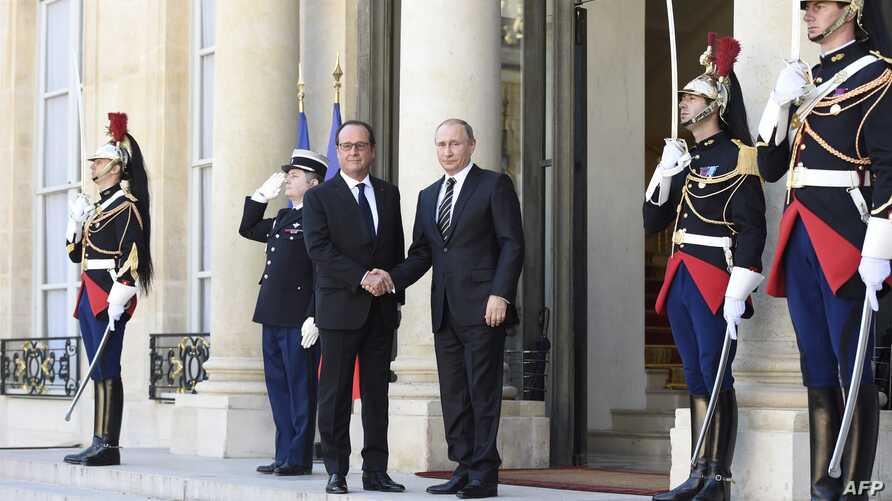 French President Francois Hollande (L) shakes hands with Russian President Vladimir Putin upon his arrival at the Elysee Palace, on Oct. 2, 2015, for a peace summit on the Ukraine conflict.
