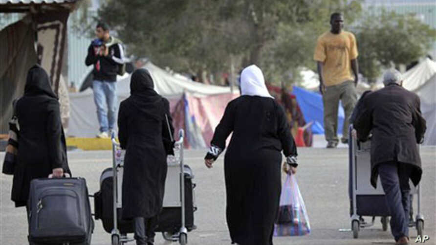 A Libyan family make their way to the terminal at the airport in Tripoli, Libya, March 17, 2011