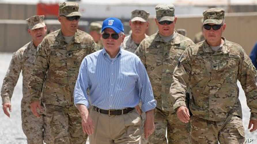 In this photo provided by ISAF Regional Command (South), U.S. Secretary of Defense Robert M. Gates walks with a group of service members at Forward Operating Base Waltman, Kandahar, Afghanistan, June 5, 2011