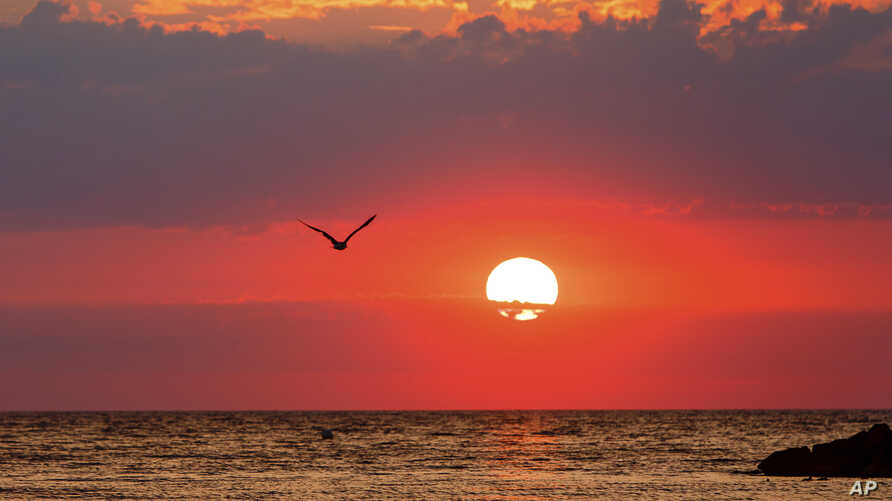 The sun sets over the Baltic Sea in Heidekate, northern Germany, July 31, 2018.