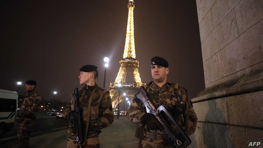 French soldiers stand guard near the Eiffel Tower in Paris on Mar. 30, 2013.