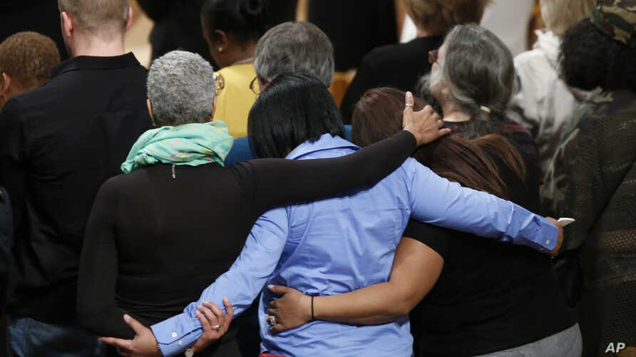 Family members of gun violence embrace each other as they hold a vigil for victims of the shooting at Sandy Hook Elementary School in Newtown, Conn., and other victims of gun violence, Thursday, Dec. 12, 2013, at the National Vigil for Victims of Gun