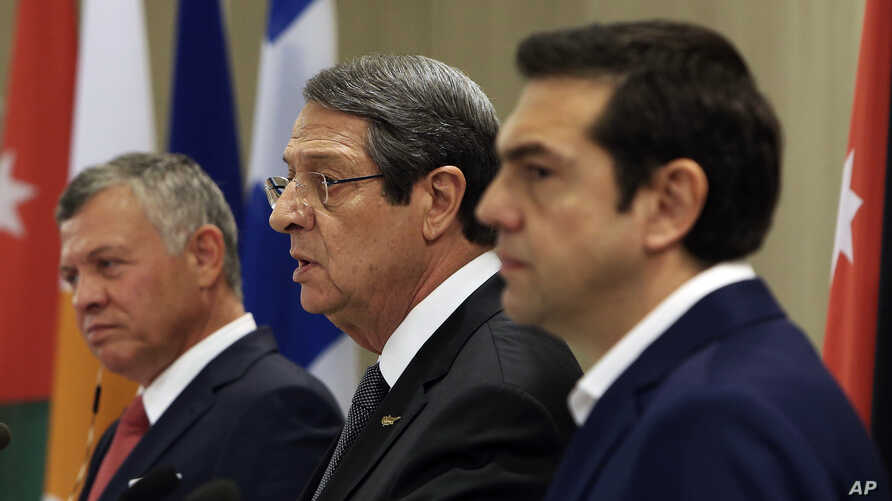 Cyprus' President Nicos Anastasiades, center, talks to the media as Jordan's King Abdullah II, left, and Greek Prime Minister Alexis Tsipras listen during a press conference at the Presidential palace in capital Nicosia, Cyprus, on Tuesday. Jan. 16,
