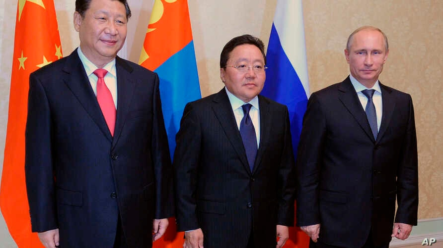 From right: Russian President Vladimir Putin, Mongolian President Tsakhiagiin Elbegdorj and Chinese President Xi Jinping pose during their meeting at the sidelines of the Shanghai Cooperation Organization summit in Dushanbe, Tajikistan, Sept. 11, 201