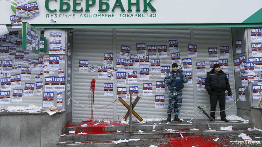 "FILE - Security staff stand guard after a protest held by members of the Azov civil corps outside the central branch of Sberbank in Kyiv, Ukraine, Feb. 2, 2017. The stickers read ""Attention. This is a bank of the aggressor state. It will be closed. I"