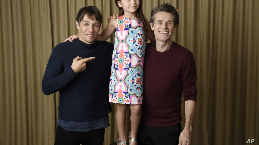 """In this Sept. 9, 2017 photo, writer-director Sean Baker, from left, actress Brooklynn Prince and actor Willem Dafoe pose together to promote their film,  """"The Florida Project,"""" during the Toronto International Film Festival in Toronto."""