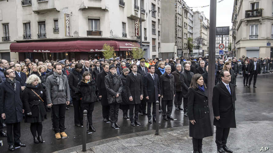 French President Francois Hollande and Paris Mayor Anne Hidalgo stand at attention after unveiling a commemorative plaque near the Petit Cambodge and Carillon cafes in Paris, France, during a ceremony held for the victims of last year's Paris attacks