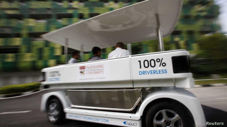 FILE - People ride on a driverless electric vehicle at the Nanyang Technological University (NTU) in Singapore.