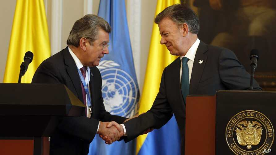 Colombia's President Juan Manuel Santos, right, shakes hands with Ambassador Elbio Rosselli, Permanent Representative of Uruguay to the United Nations, after a joint statement at the presidential palace in Bogota, Colombia, May 4, 2017.