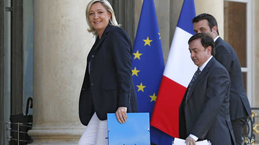 FILE - In this May 16, 2014 photo, French Front National party president Marine Le Pen, left, and vice-presidents Jean-Francois Jalkh, center, and Florian Philippot arrive at the Elysee Palace for a meeting with French President Francois Hollande in