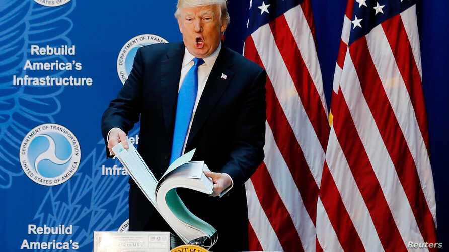 U.S. President Donald Trump pages through a document of U.S. government regulations before delivering remarks on regulatory relief at the Department of Transportation in Washington, June 9, 2017.
