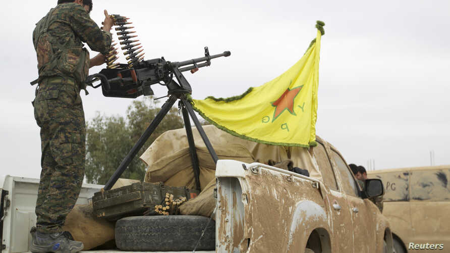 FILE - A Kurdish fighter is seen atop a pickup truck near the city of Ras al-Ain, Syria, November 5, 2013.