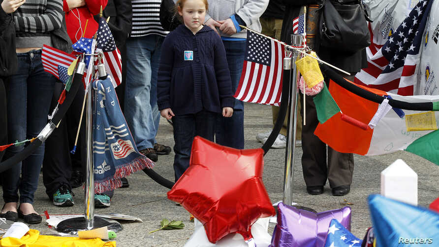 A young girl looks at a memorial to the victims of the Boston Marathon bombings on Boylston Street near the scene of the blasts in Boston, Massachusetts, Apr. 20, 2013.