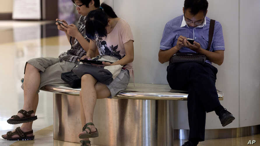 FILE - People sit on a bench inside a shopping mall using their mobile devices, in Beijing, China, Aug. 19, 2013.