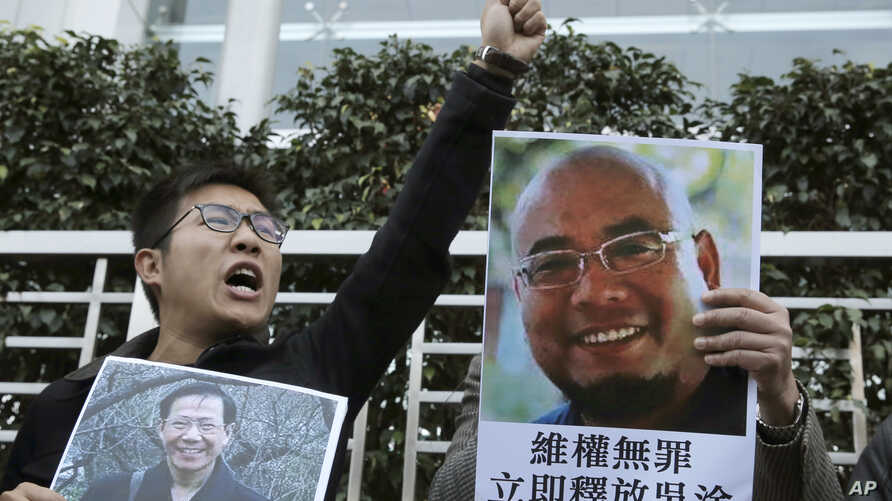 FILE - Pro-democracy activists hold pictures of Chinese activists Wu Gan, right, and Qin Yongmin outside the Chinese central government's liaison office in Hong Kong, Dec. 27, 2017.