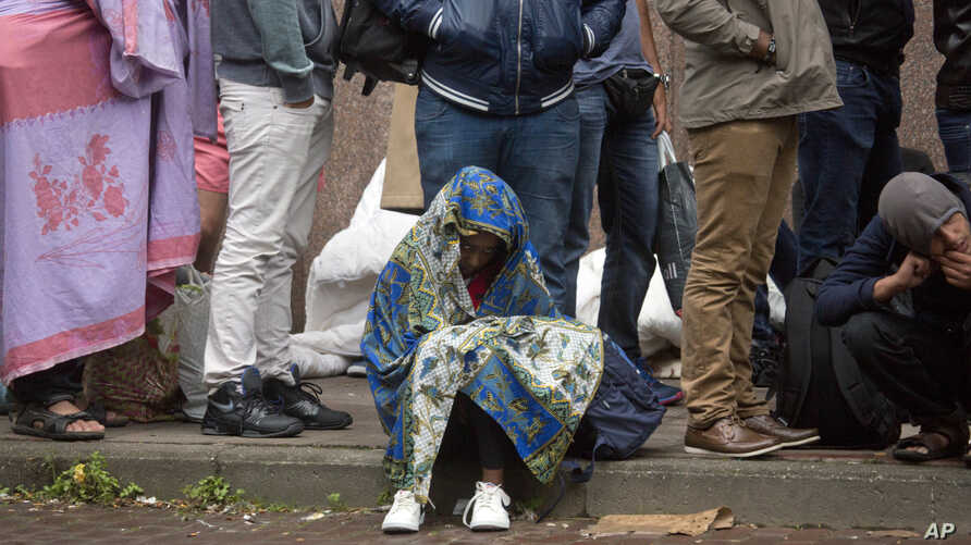 FILE - In this Sept. 1, 2015 file photo, a young child waits in line at a migrant reception center in Brussels. Belgian migration minister Theo Francken on Dec. 6, 2018, said he wants no part of a United Nations pact on safe and orderly migration.