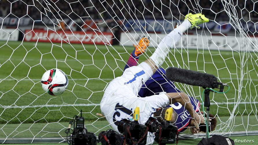 Japan's Shinji Okazaki (R) and Uzbekistan's Lutfulla Turaev dive into the net after Japan's Gaku Shibasaki (not in picture) scored during their international friendly soccer match in Tokyo March 31, 2015. REUTERS/Yuya Shino      TPX IMAGES OF THE DAY...