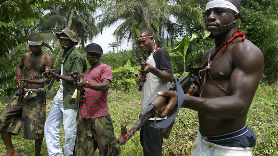FILE- Militants stand guard at Okorota, near Port Harcourt, Nigeria. Nigeria's government resumed paying stipends to former militants in August 2016, even as security forces reported killing scores of fighters disrupting petroleum production in the o