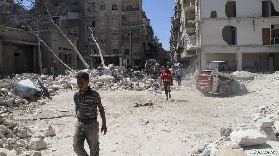 People walk on rubble of buildings damaged by what activists said was shelling by forces loyal to Syria's President Bashar al-Assad in Aleppo's Bustan al-Qasr district, Sept. 9, 2013.