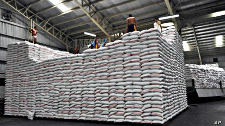 Workers piling sacks of rice at a government rice warehouse in Manila (file photo)