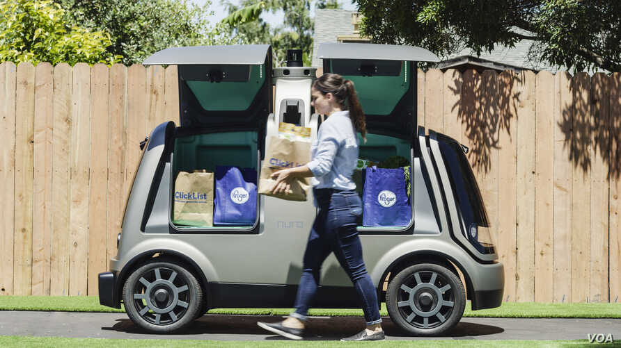 A woman walks in front of an unmanned delivery vehicle known as the R1 is seen in this handout photo provided by Kroger.