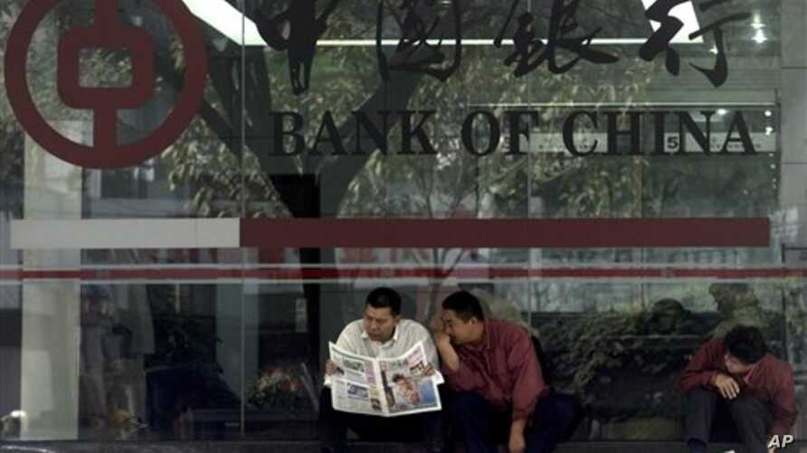 In this undated file photo, men in Guangzhou, southeastern Guangdong province, share newspaper outside a branch of the state-run Bank of China, which recently halted business with the Foreign Trade Bank of North Korea in the latest sign of Beijing's
