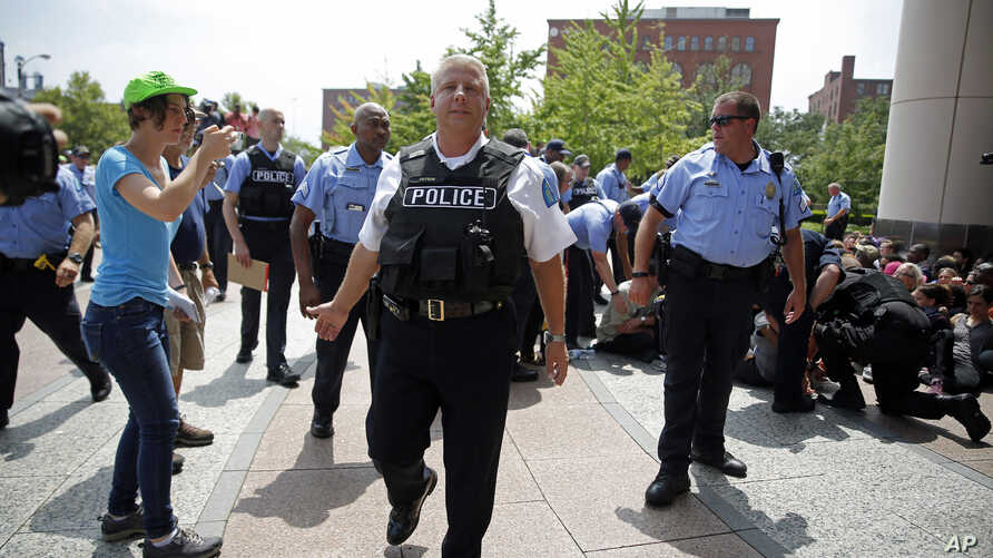 St. Louis police chief Sam Dotson pushes the media and others back as protesters are arrested outside the Thomas F. Eagleton Federal Courthouse Aug. 10, 2015, in St. Louis.