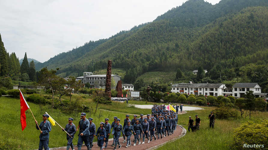 Participants dressed in replica Red Army uniforms march during a Communist team-building course extolling the spirit of the Long March, organized by the Revolutionary Tradition College, in the mountains outside Jinggangshan, Jiangxi province, China,
