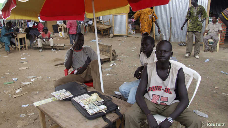 A money changer waits to do business at his open-air stall at a market in Juba, South Sudan, April 9, 2007.