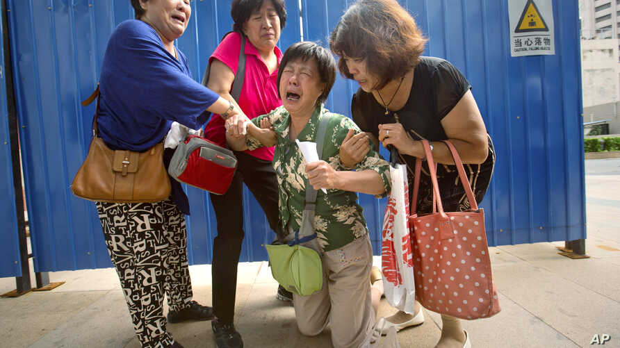 Bao Lanfang, second from right, whose daughter-in-law, son, and granddaughter were aboard Malaysia Airlines Flight 370, kneels in grief while speaking to journalists outside the company's offices in Beijing, Thursday, Aug. 6, 2015.