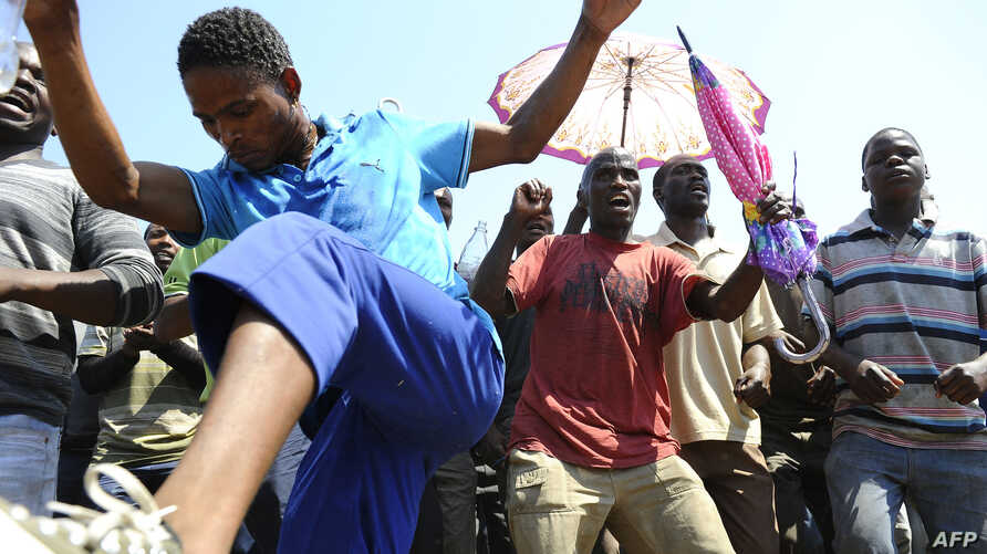 Striking mine workers protest outside the Anglo American Mine in Rustenburg, South Africa, October 5, 2012.
