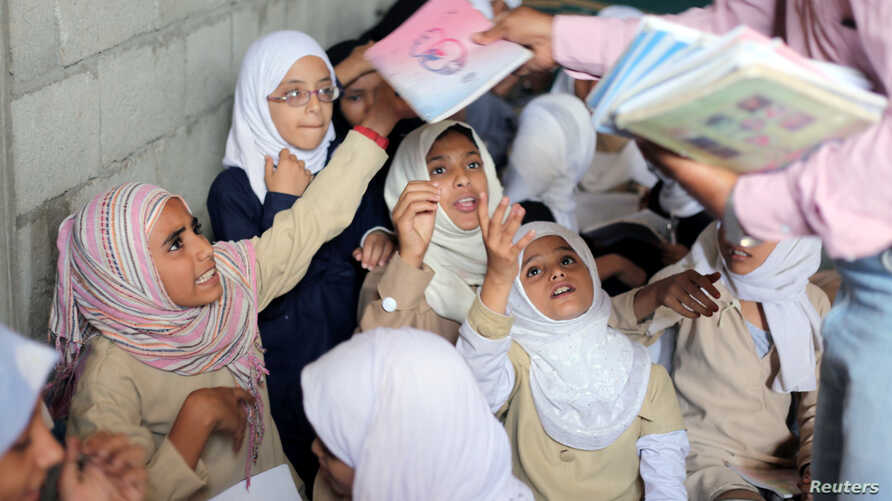 Students receive books in their class at the teacher's house, who turned it into a makeshift free school that hosts 700 students, in Taiz, Yemen, Oct. 18, 2018.
