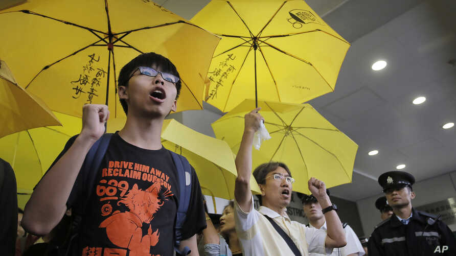 Hong Kong teenage student leader Joshua Wong, left, shouts slogans with supporters outside a magistrates' court in Hong Kong, Wednesday, Sept. 2, 2015.
