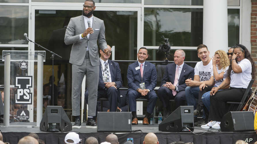 LeBron James speaks and gets a laugh from his mother, Gloria, right, at the opening ceremony for the I Promise School in Akron, Ohio, July 30, 2018.