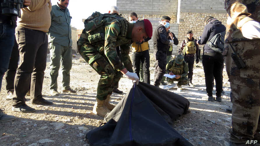 A member of Iraqi security forces put in a plastic bags the remains of people killed by the Islamic State group that were found in a mass grave on Jan. 26, 2016, a day after it was discovered in the Al-Jamiya area of central Ramadi.
