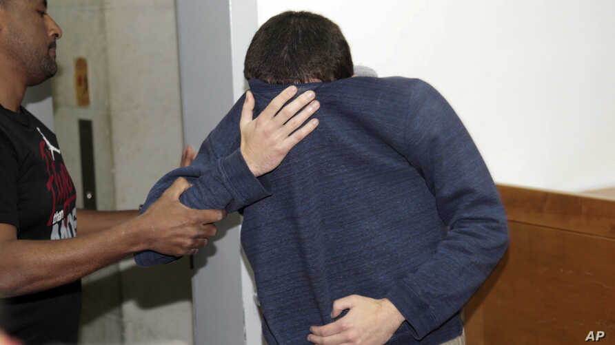 FILE - A 19-year-old dual U.S.-Israeli citizen covers his face as he is brought to court in Rishon Lezion, Israel, March 23, 2017. Israeli police said they have arrested a Jewish Israeli man who is the prime suspect behind a wave of bomb threats agai