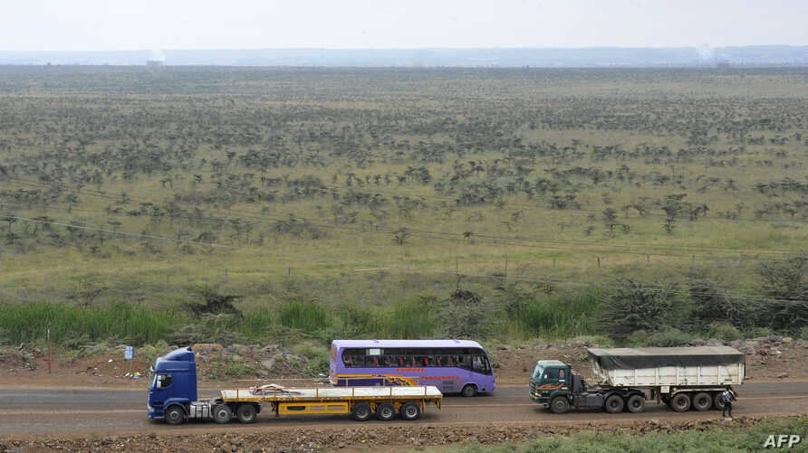 Trucks and buses drive past the area in Nairobi where Kenya's new Chinese-built rail line will cut through the capital's sprawling sanctuary for lions, giraffes and zebras, Aug. 4, 2015.