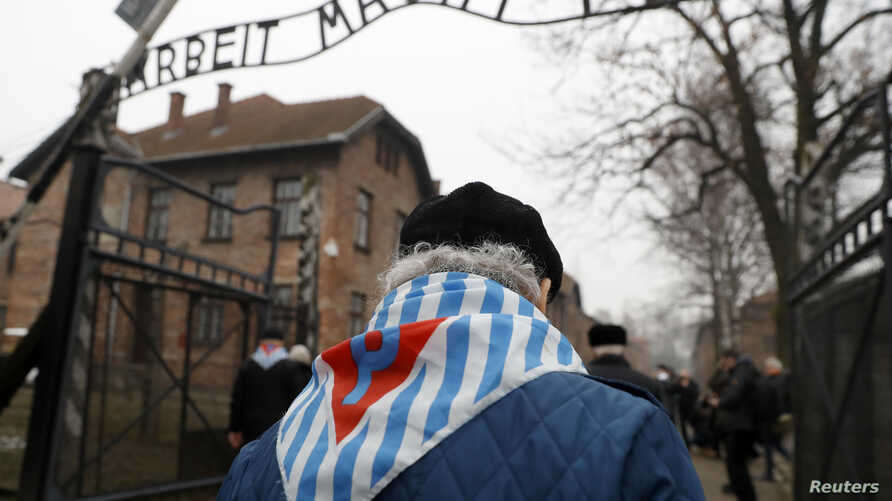 """Survivors and guests walk past the """"Arbeit Macht Frei"""" (""""Work Sets You Free"""") gate at the former Nazi German concentration and extermination camp Auschwitz, during the ceremonies marking the 73rd anniversary of the liberation of the camp and Internat"""