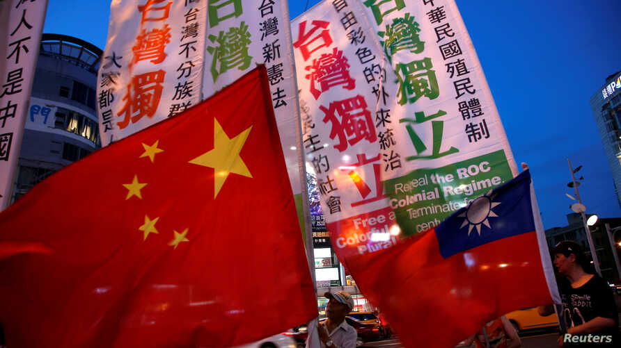 FILE - Members of a Taiwanese independence group march with flags around a group of pro-China supporters holding flags during a rally, in Taipei, May 14, 2016.