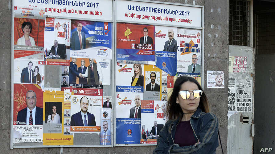 A woman walks past election posters on March 29, 2017 in Yerevan, ahead of April 2 parliamentary elections.