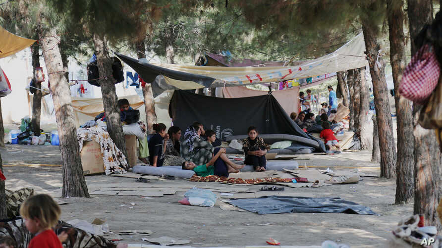 Displaced Iraqis from the Yazidi community gather at a park near the Turkey-Iraq border at the Ibrahim al-Khalil crossing, as they try to cross to Turkey on Aug. 15, 2014.