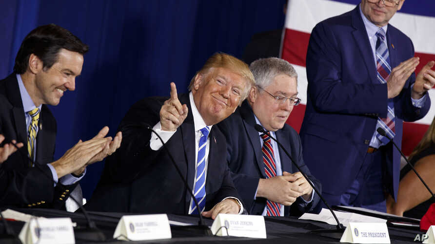 President Donald Trump smiles as people applaud him during a round-table discussion on tax policy, April 5, 2018, in White Sulphur Springs, W.Va. From left are Rep. Evan Jenkins, R-W.Va., West Virginia Attorney General Patrick Morrisey, and CEO of Da...