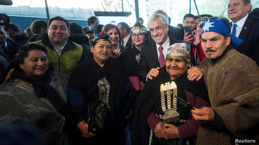 Chile's President Sebastian Pinera poses along with Mapuche indigenous community members during an official ceremony in Temuco, Chile, Sept. 24, 2018.