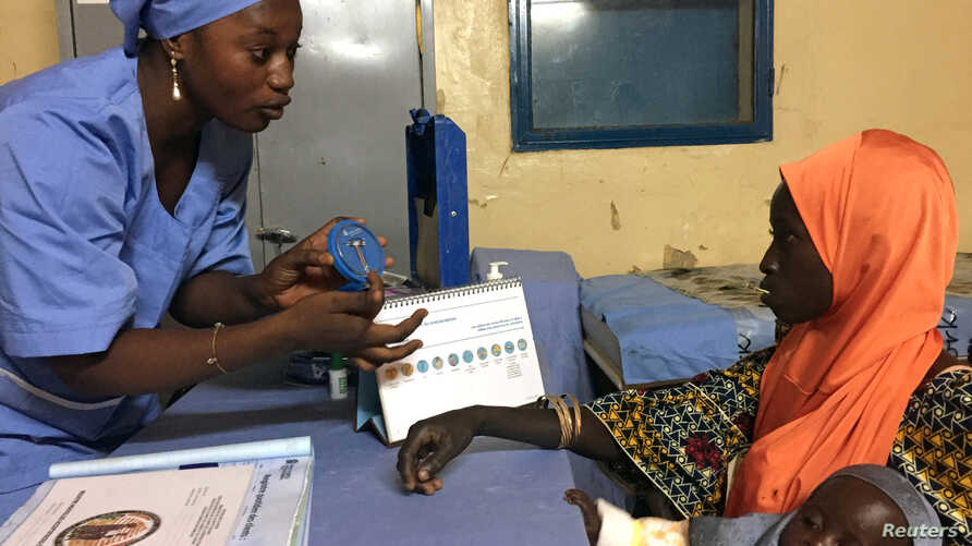 FILE - A nurse explains to mother-of-three Kadidja Toudjani how a contraceptive implant works, in Libore, Niger, Nov.  2, 2017.