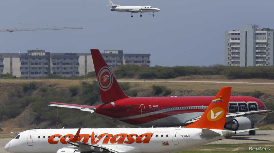 Airplanes wait their turn to take off on a runway of the Simon Bolivar airport in La Guaira, outside Caracas, Venezuela, Sept. 23, 2013.