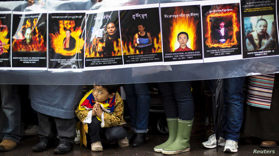 A child gestures at the feet of protesters holding a sign commemorating victims of self-immolation during a solidarity march from the Chinese Consulate to the United Nations (UN) Headquarters in support of Tibet in New York December 10, 2012.
